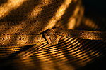 Sun hat in sunrise light on table with light streaks and close up of knot