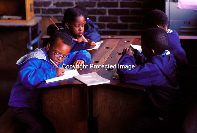 dieduca00139 Education, School, Classroom: Unidentified children studying in a class room on July 12, 2002 at a Catholic school in Soweto, a black township outside Johannesburg, South Africa. Soweto is the largest township in the country and itÕs estimated that about 3-4 million people resides there..©Per-Anders Pettersson / iAfrika Photos...