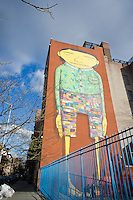 A multi-national themed mural by the Brazilian graffiti artists Os Gémeos, The Twins in English, decorates the side of a school in the New York neighborhood of Chelsea, seen on Thursday, March 29, 2012. Brazilian brothers Otavio and Gustavo Pandolfo, who call themselves Os Gémeos, created the mural. (© Richard B. Levine)