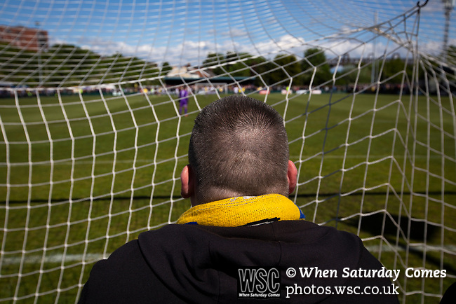 A visiting supporter watching the first-half action as Warrington Town played King's Lynn Town in the Northern Premier League premier division super play-off final tie at Cantilever Park, Warrington. The one-off match was between the winners of play-off matches in the Northern Premier League and the Southern League Premier Division Central to determine who would be promoted to the National League North. The visitors from Norfolk won 3-2 after extra-time, watched by a near-capacity crowd of 2,200.