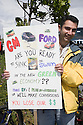 A protestor holding a sign at a Step It Up 2007 protest rally for increased vehicle fuel efficiency to help to reduce CO2 emissions in relation to climate changes. The sign addresses General Motors (GM) and Ford which are American automakers, reading 'GM, Ford Are You Ready to Sink or Swim in the New Green Economy?' San Rafael, California, USA