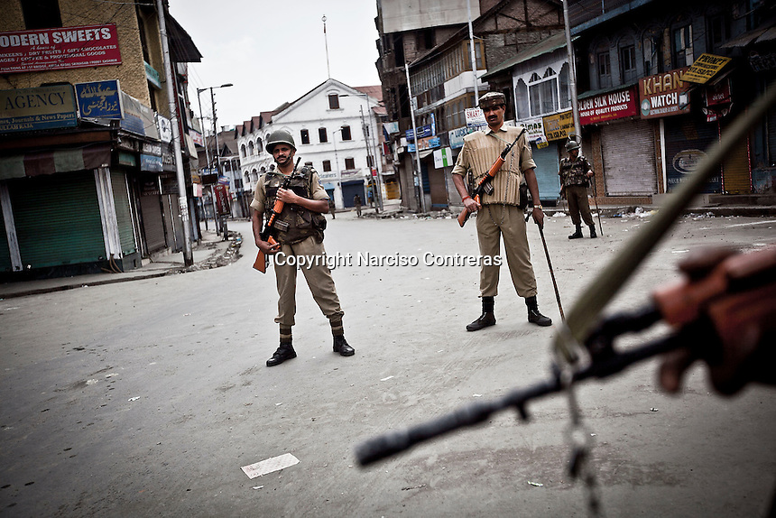 Indian paramilitary soldiers stand guard at a check point in Srinagar as India is celebrating the Independence day. The curfew was declared into the most conflictive areas across the city and districts into the Kashmir valley. Security has been beefed up by indian paramilitary forces (CRPF), army and police on streets and check points.