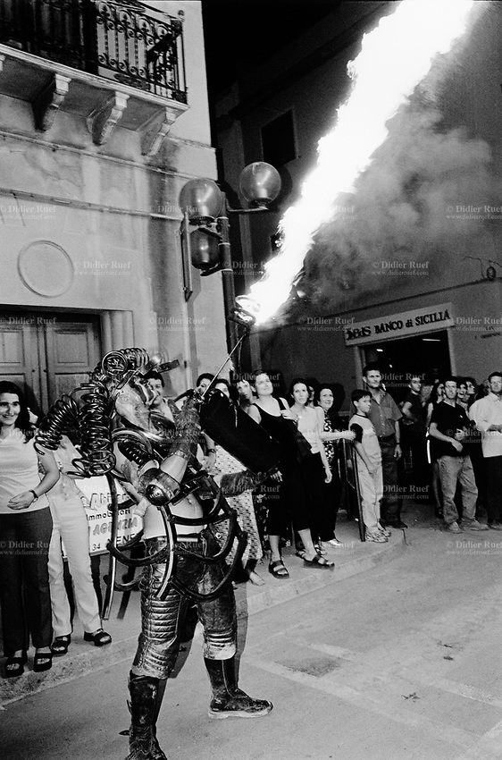 "Italy. Province of Sicily. Menfi. Mutoid Waste Company. A man shoots flames in the air from a modified fire extinguisher during a show at ""Inycon"" festival. Using all types of industrial scrap for their raw materials the Mutoid Waste Company are a mobile and adaptable group of performance artists. Having the necessary equipment to allow them complete freedom, they have created an entirely new form of scultural-musical performance crossing the boundaries of circus, theatre and art. © 1999 Didier Ruef / pixsil.com"