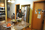 Bianca Tobar, 25, makes a salad for dinner with her mom in the kitchen of her family's house in the Bridgeport neighborhood in Chicago, Illinois on April 22, 2015.  Tobar works as an administrative assistant a doctor at a medical center.