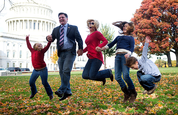 UNITED STATES - NOVEMBER 04: Rep. Luke Messer, R-Ind., his wife Jennifer, and their children Ava, 9, left, Emma, 10, and Hudson, 6, leap during a family photo shoot on the east lawn of the Capitol. (Photo By Tom Williams/CQ Roll Call)