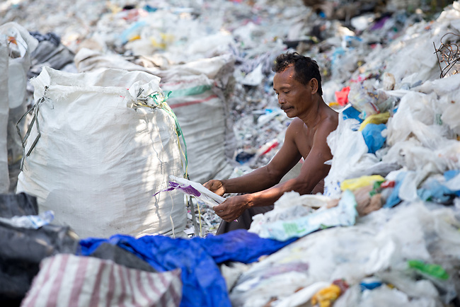 21 May 2019, Bangun Village,East Java, Indonesia: Sucipto (55) a rag picker looks at Australian branded waste in dumps at Bangun Village outside Surabaya, Indonesia. Millions of tonnes of recyclable plastic trash from Australia and Europe is dumped for rag pickers to separate and sort. The plastics are used to fuel fires at local tofu factories among other industries. Australia is illegally sending non recyclable trash hidden within this lode and the Indonesian Government is cracking down on the practice and preparing to refuse to take Australia's rubbish that is creating environmental and health issues locally. Picture by Graham Crouch/The Australian