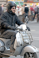 A scooter rider on a Vespa PX in the centre of Rome.