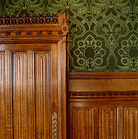Detail of the green flock wallpaper in the Lord Chancellor's apartments, its rich pattern echoing Pugin's intricate gothic carving on the door frame