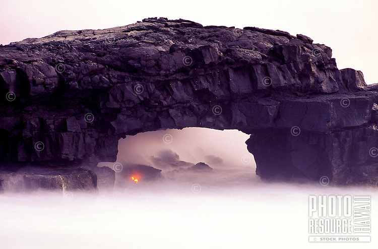 An arch of hardened lava appears to float in white mist at Volcanoes National Park on  the Big Island of Hawaii