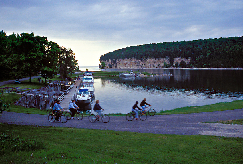 A FAMILY BIKES PAST BOATS DOCKED IN SNAIL SHELL HARBOR AT FAYETTE STATE HISTORIC PARK ON THE GARDEN PENINSULA.