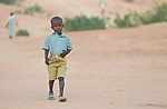 A boy walks to school in Kauda, a village in the Nuba Mountains of Sudan. The area is controlled by the Sudan People's Liberation Movement-North, and frequently attacked by the military of Sudan. The Catholic Church sponsors schools and health care facilities throughout the war-torn region.
