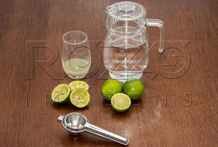 Preparando uma limonada com espremedor, limões inteiros e espremidos, uma jarra de água e um copo suco de limão, São Paulo - SP, 10/2016.