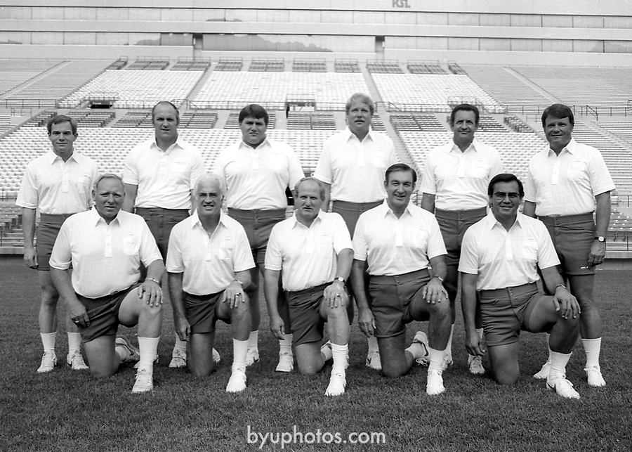 FTB 1984 Photoday<br /> Team Coaches<br /> FTB 700 ii 4<br /> <br /> Standing Row: Chuck Stiggins, Mel Olsen, Lance Reynolds, Mike Holmgren, Ken Schmidt, Jim Paronto<br /> Kneeling Row: Tom Ramage, Dick Felt, LaVell Edwards, Roger French, Norm Chow<br /> <br /> Photo by Mark Philbrick/BYU<br /> <br /> © BYU PHOTO 2009<br /> All Rights Reserved<br /> photo@byu.edu  (801)422-7322