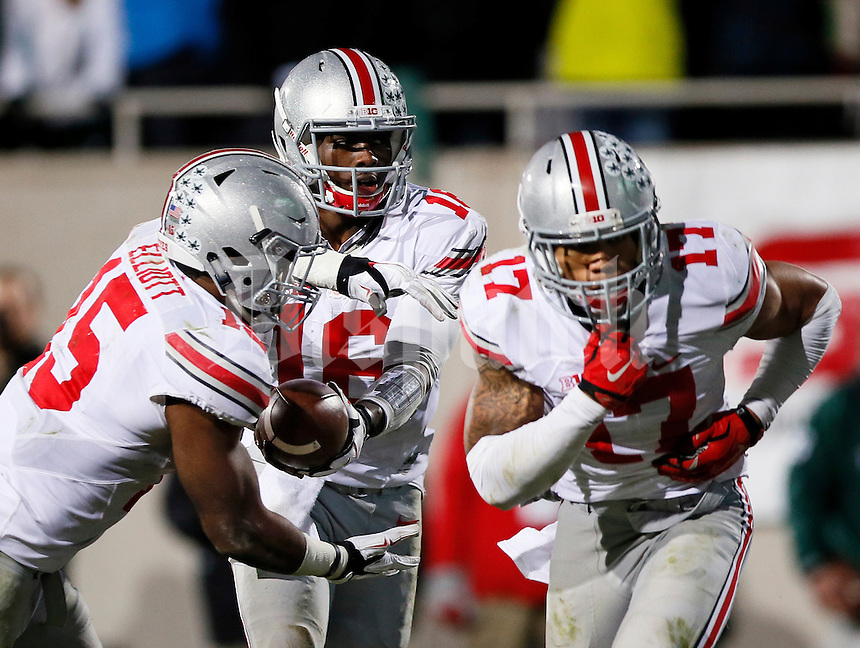 Ohio State Buckeyes quarterback J.T. Barrett (16) fakes the handoff to running back Jalin Marshall (17) and gives it to running back Ezekiel Elliott (15) during Ohio State's 49-37 win over Michigan State in the NCAA football game at Spartan Stadium in East Lansing, Michigan on Nov. 8, 2014. (Adam Cairns / The Columbus Dispatch)