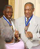 Hank Aaron and Bill Cosby accept congratulations after they received the Presidential Medal of Freedom from United States President George W. Bush during a ceremony in the East Room of the White House in Washington, D.C. on July 9, 2002..Credit: Ron Sachs / CNP