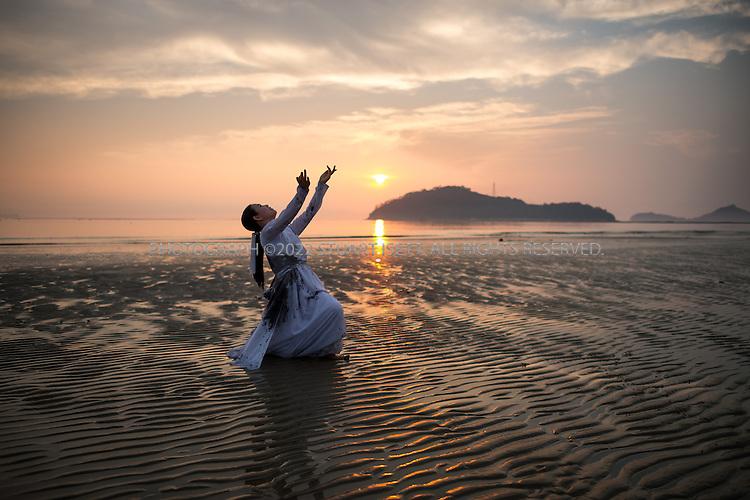 9/9/13 -- Songho Beach, Haenam, Jeonnam Province (Jeollanam-do), South Korea<br /> <br /> Street dancer Youngja Kim performs on Songho Beach.<br /> <br /> Photograph by Stuart Isett<br /> &copy;2013 Stuart Isett. All rights reserved.
