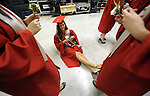 Jessica Robitaille relaxes sitting on the floor as grads hold the boutonnieres  they just received,   prior to the start start of the  graduation ceremony, Thursday, June 20, 2013, in Hartford. (Jim Michaud / Journal Inquirer)