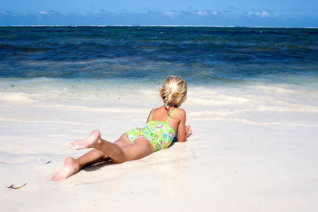 Africa, Kenya, Malindi.  Young girl relaxes on the beach while watching the ocean on the coast of Kenya. MR