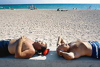 "Spain. Mallorca in the Balearic islands. Palma. Two men, both tourists , take a rest, sunbathe and sleep, stripped to the waist, on a concrete wall in the sandy beach of "" Playa de Palma"". © 1999 Didier Ruef"
