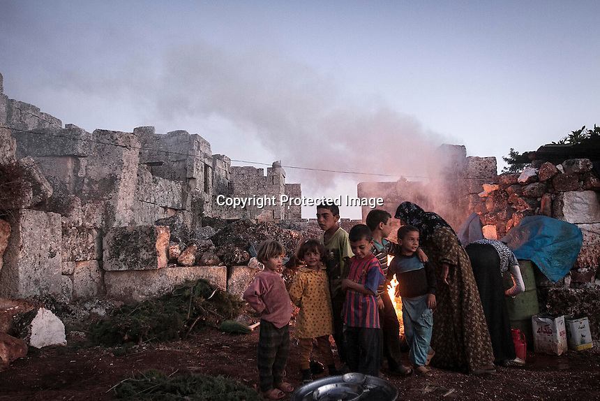 "In this Thursday, Sep. 26, 2013 photo, a Syrian displaced family cook a meal for dinner as children play in the sunset at the Kafr Ruma, an ancient roman ruins used as temporary shelter by those families who have fled from the heavy fighting and shelling in the Idlib province countryside of Syria. Dozens of families settled in the ancient ruins known as ""The Forgotten City"" and declared human heritage by UNESCO, when the clashes between opposition fighters and government forces broke out in the region since more than two years ago. (AP Photo)"