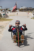 Morehead City, NC -- Quadriplegic hand cyclist Paul Kelly, 62, climbs a hill as he trains for the Boston Marathon Tuesday, March 27, 2018. (Justin Cook for The Wall Street Journal)<br /> <br /> SUMMARY:<br /> <br /> Paul Kelly, hand cyclist, Beaufort, NC Training for the Boston Marathon so we would want to shoot in March to run the week before the marathon or marathon Monday, Apriln16. Life as a quadriplegic doesn't keep 62-year-old Paul Kelly on the sidelines. After breaking his neck in a swimming accident in 1978, Kelly was determined to find fitness activities to maintain an active lifestyle. He discovered handcycles while watching his niece compete in the 2006 Marine Corps Marathon and was inspired to start his own marathon career to stay fit. Paul has competed in over 100 half and full marathons. On April 16, he will celebrate his 40th year of living as a quadriplegic by taking on one of the most coveted races for a marathoner -- the Boston Marathon. Kelly is among the 60 handcyclists competing in the 2018 Boston Marathon with a qualifying time of 1:26:37. Most of Paul's distance training takes place at Bogue Banks, which includes Atlantic Beach, Salter Path, and Emerald Isle, N.C. It's Nicholas Sparks worthy scenery with its marshes, waterways, inlets and small islands. Paul is particularly fond of the approach from Atlantic Beach to Bogue Banks -- it's via the high-rise bridge. In cold weather, Paul has to be mindful of the environment and dress in a manner that insulates his legs while also allowing his upper body to ventilate. Paul chooses to train at times of day when the temperatures are more reasonable. He uses hand warmers in his gloves, on the inside the grips on his handcycle and in the legs of his trousers.