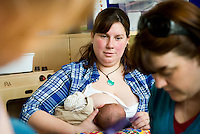 "A mother breastfeeding her baby at a drop-in breastfeeding support centre, with a breastfeeding consultant in the foreground.<br /> <br /> Image from the ""We Do It In Public"" documentary photography project collection: <br />  www.breastfeedinginpublic.co.uk<br /> <br /> Dorset, England, UK<br /> 17/04/2013"