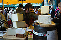 London, UK. 25.10.2014. A man serving customer on a cheese stall on Borough Market, Southwark. Photograph © Jane Hobson.