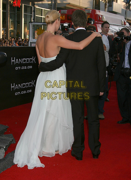 """CHARLIZE THERON & STUART TOWNSEND .""""Hancock"""" Los Angeles Premiere held at the Grauman's Chinese Theatre, Hollywood, California, USA, .30 June 2008..full length strapless blue pale dress back rear behind couple arms around back shoulder.CAP/ADM/MJ.©Michael Jade/Admedia/Capital Pictures"""