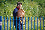 "© Joel Goodman - 07973 332324 . Stockport , UK . Veterinary surgeon SIMON CONSTABLE carries the tranquilised deer from the playground area in the park . A wild deer which was discovered in a park by the busy Manchester Road in Stockport has been rescued after three days . The park was closed and locked by Stockport Council officials on Monday 24th June after the young male started bolting across the playing field and playground and butting its head and antlers against railings . But with the gates locked , the young animal could not escape . For three days local people came out to watch the deer from the fence as it hid in bushes around the edge of the park , occasionally venturing out across the playing pitch and in the direction of the busy A626 road . The landlord at "" The Hind's Head "" pub opposite , Stuart Kirkham , a Manchester United fan , named the beast "" Ronaldo "" because of its red colouring . After three days , with no hope of escape under its own steam and with the park still closed , the RSPCA and council brought in a veterinary surgeon to help . The animal was tranquilised and driven to nearby Reddish Vale Country Park , where he was brought round and released back in to the wild . Photo credit : Joel Goodman"