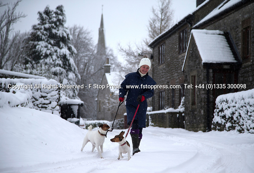 21/01/15<br /> <br /> A woman walks her dogs in Monyash, Derbyshire.<br /> <br /> More than 20 schools in Derbyshire were closed today following overnight snowfall that continued into the morning across the Peak District.<br /> <br /> All Rights Reserved - F Stop Press.  www.fstoppress.com. Tel: +44 (0)1335 300098