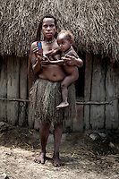 Christiana Margaretipo, 21, with her son, holds a mobile phone. She shares the phone with her brother and often calls her relatives in other villages of the Baliem Valley.