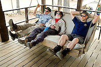Photo story of Philmont Scout Ranch in Cimarron, New Mexico, taken during a Boy Scout Troop backpack trip in the summer of 2013. Photo is part of a comprehensive picture package which shows in-depth photography of a BSA Ventures crew on a trek. This photo show BSA Venture Crew adult advisors relaxing in a porch swing, after a long day of hiking. The advisors had just arrived and checked in at staff camp in the backcountry of the Philmont Scout Ranch.<br /> <br /> The  Photo by travel photograph: PatrickschneiderPhoto.com