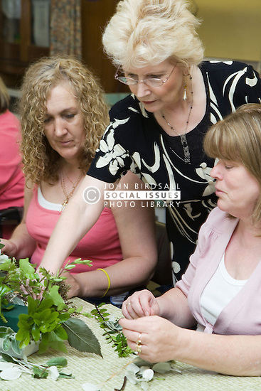 Volunteer tutor showing how to make a flower arrangement,