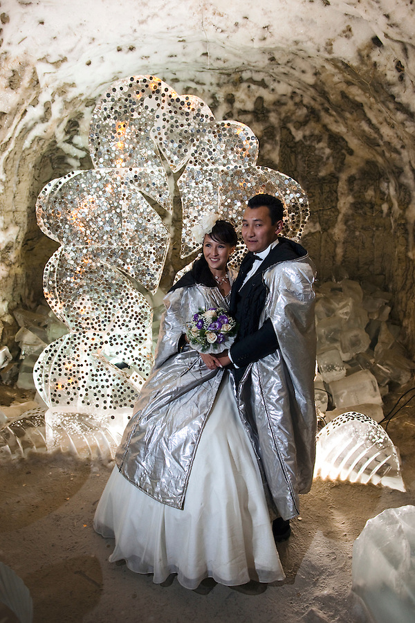 Yakutsk, Yakutia, Russia, 19/08/2011..Newly-weds Nadezhda and Vasily Fedorov with an ice sculpture of a money tree inside the Permafrost Kingdom, an underground tourist attraction inspired by the extreme cold of Yakutia. The 150 metre deep complex of tunnels in the Russian permafrost are decorated with ice sculptures, a wolf-fur covered throne, an office complete with the coolest computer and telephone, a children's slide and other ingenious creations - all hewn from blocks of ice.