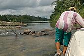 Pará State, Brazil. Boatman Doto pulling the Coração do Brasil over shallow rocky rapids.