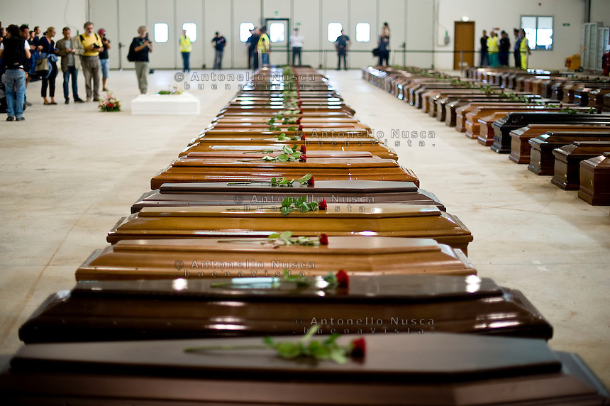 Le bare dei 110 clandestini morti nel naufragio al largo delle coste di Lampedusa, nell'hangar dell'aeroporto. Roses are displayed on coffins of victims in an hangar of Lampedusa airport on October 5, 2013 after a boat with migrants sank killing more than hundred people.