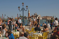 Tourists walking by and sitting at tables opposite, San Giorgio Maggiore on the Grand Canal. Venice, Italy, May 2007.