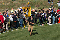 A membe of the Mizzou cross country program runs the course carry a Mizzou flag at the 2016 NCAA Division I Cross Country Midwest Regional.