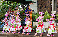 Young girls wearing pink plumeria lei and haku head lei perform a hula with live music in Hale'iwa, North Shore, O'ahu.