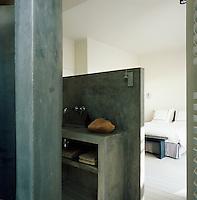 A concrete partition unit encompassing a hand basin and shelving separates a bathroom area from a bedroom.