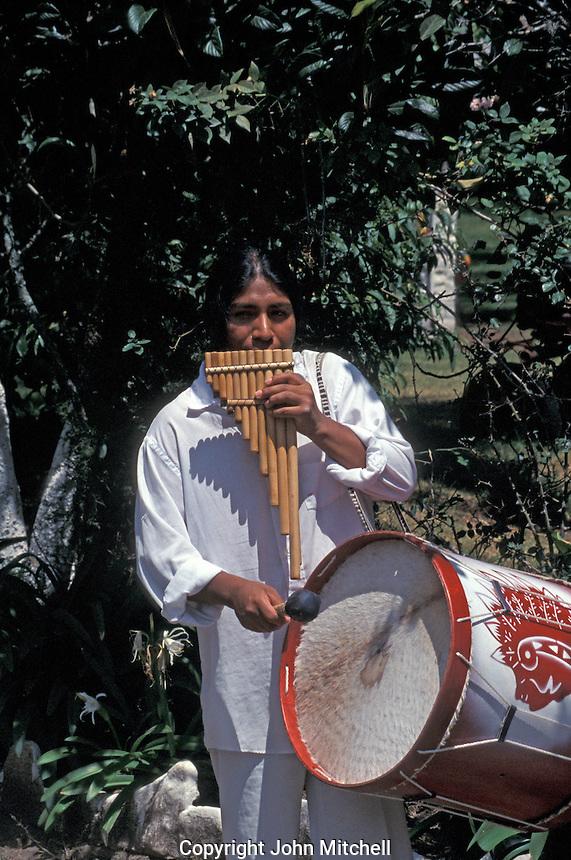 Ecuadorean musician playing traditional bamboo panpipes or rondadores and a drum, Ecuador, South America