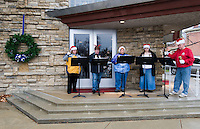 A choir of bell ringers perform in front of a church in Westerville, Ohio, before the annual Christmas parade arrives during a wet, rainy parade.  Photo Copyright Gary Gardiner. Not for reproduction without written permission.