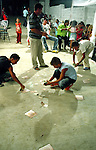 The young boys collect money on the floor that was donated by invitees. The money will be given to the band. Elbasan, Albania.