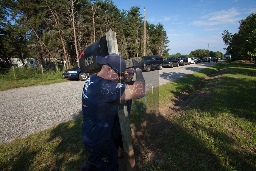 Rowdy Shaw (left) and Perry Stone move a mailbox to enable parking of a HSUS rig during a raid on a puppy mill in Johnston, SC on Tuesday, Sept. 11, 2012. HSUS workers found over 200 dogs, nine horses and 30-40 fowl.