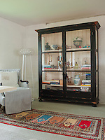 A new glass-fronted cabinet in the living room could pass for an antique, with its distressed black paintwork and panelled back
