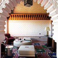 View through an arch to a small sitting room decorated with ornate plasterwork and an intricately carved wooden cornice