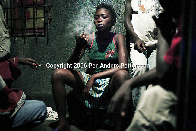 KINSHASA, DEMOCRATIC REPUBLIC OF CONGO - MAY 4: Betty Nginamawu, age 14, smokes marijuana in a drug house on May 4, 2006 in Matonge district in central Kinshasa, Congo, DRC. Betty is homeless and works as a prostitute together with four friends. The girls live outside next to a polluted river. Betty has been on the streets for a few years, and has been rejected by her family. From time to time, she lives in a homeless shelter for but doesn't like the rules there. She was recently rejected from the shelter as she brought in Valium to give the other girls. She usually smokes cigarettes, marijuana and drinks whiskey. She charges the clients as little as US$ 1. About 15,000 children are estimated to live on the streets of Kinshasa. Congo, DRC is in ruins after forty years of mismanagement by the corrupt dictator and former president Mobuto Sese Seko. He fled the country in 1997 and a civil war started. The country is planning to hold general elections by July 2006, the first democratic elections in forty years.(Photo by Per-Anders Pettersson)