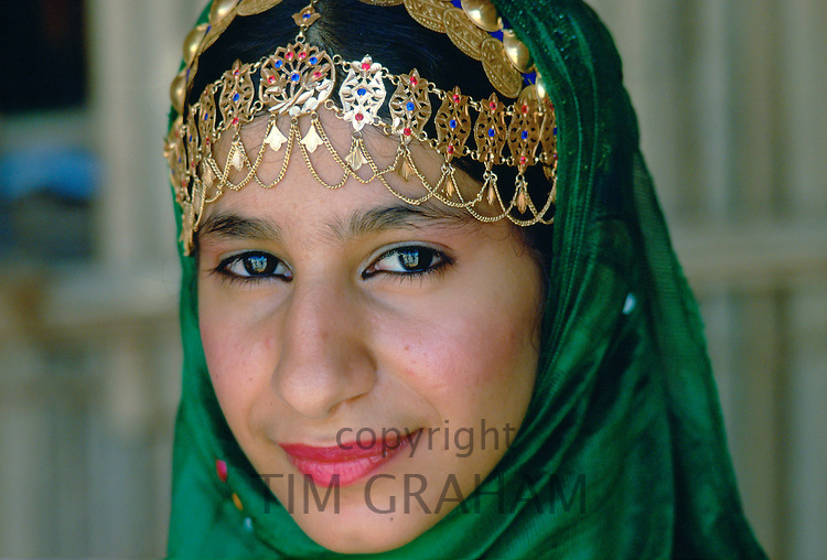 An Omani woman wearing gold jewels and a veil, Nizwa, Oman
