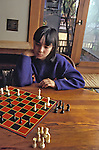 Berkeley CA Latina girl, 10 years old, studying her next chess move at home MR