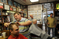 STAFF PHOTO FLIP PUTTHOFF<br /> HAIRCUTS FOR CHARITY<br /> Spencer Fox, left, and Ray Birchfield, in chair at right, get trimmed by barbers Vic Bradford, second from left, and Gary Townzen, third from left, during the annual free haircut day on Saturday Dec. 20 2014 at Townzen Barbershop in downtown Rogers. Donations were accepted to benefit Samaritan Community Center. This is the 28th year that Townzen, shop owner, has held the free haircut event.